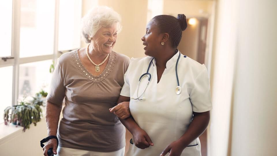 Elderly lading smiling with a nurse in a corridor