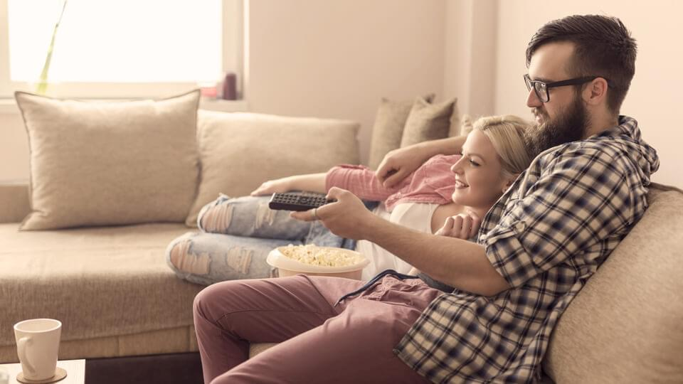 Young couple watching a movie and having popcorn
