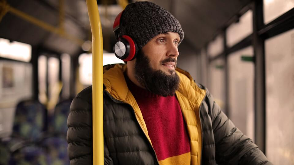 Man, wearing cold weather clothes on public transport wearing headphones