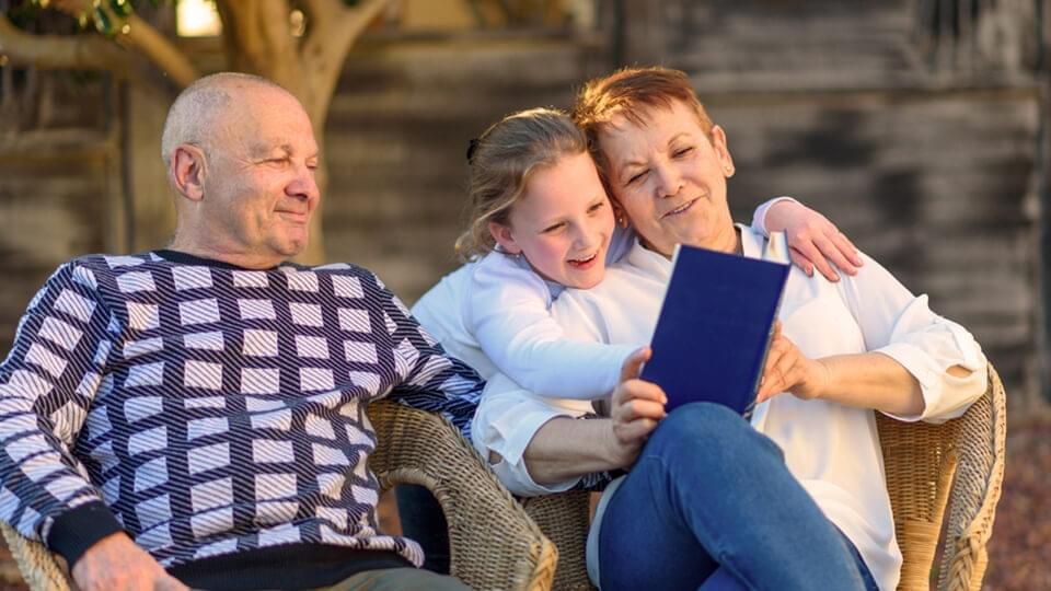 Family happily sitting outside, reading book